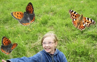 girl watching butterflies and smiling