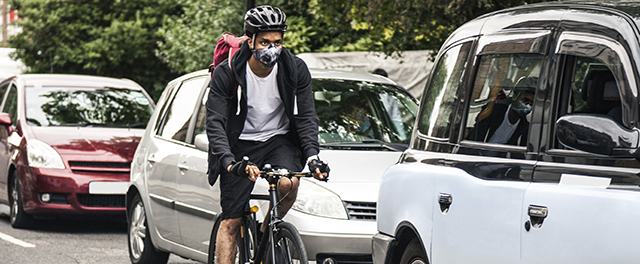 Cyclist in traffic with mask