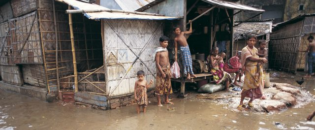 People stand outside their flooded home